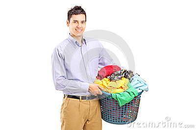 A smiling man holding a laundry basket
