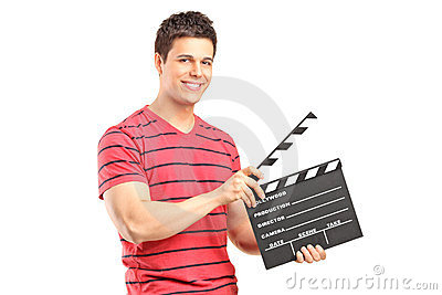 A smiling man holding a movie clap