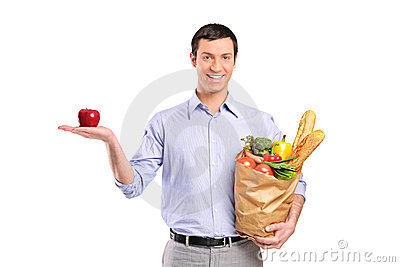 Smiling man holding a red apple and a bag