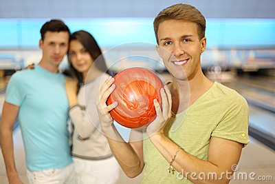Smiling man holds ball; pair stands behind him