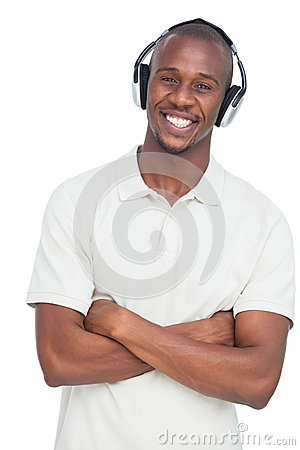 Smiling man listening to music with arms crossed