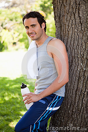 Smiling man looking to the side while holding a sports bottle an