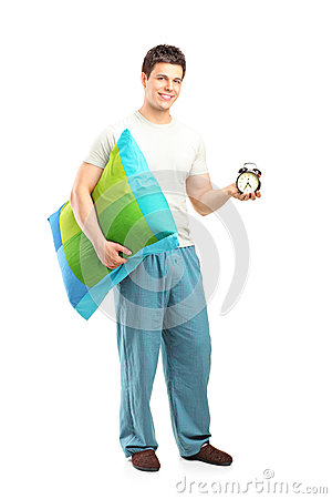 Smiling man in pajamas holding a pillow and alarm clock