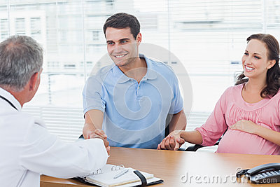 Smiling man shaking hands with his doctor while holding his expe