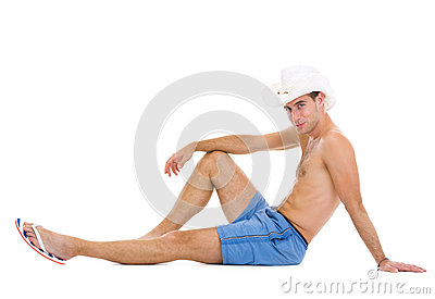 Smiling man in shorts and hat sitting on floor