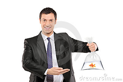 A smiling man showing a plastic bag with fish