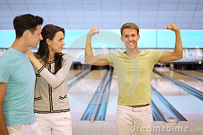 Smiling man shows arm muscles; pair look at him