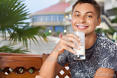 Smiling man sitting and drinking kefir