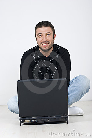 Smiling man sitting on floor with a laptop