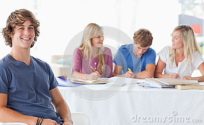 Smiling man sitting on front of his friends