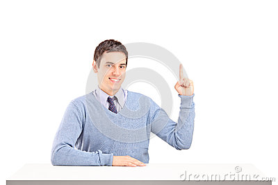 Smiling man sitting and pointing with finger