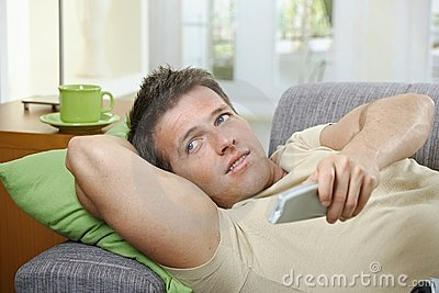 Smiling man on sofa using remote control