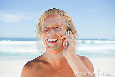 Smiling man using his mobile phone while standing on the beach