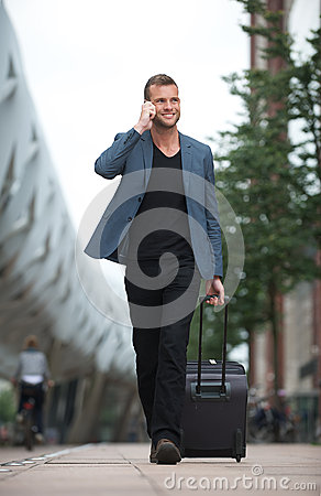 Smiling Man Walking in City with Cell and Suitcase