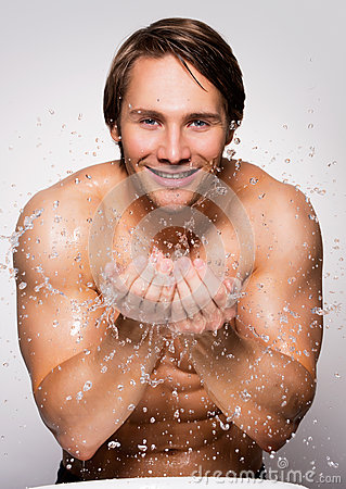 Free Smiling Man Washing His Healthy Face With Water. Stock Photography - 61778272
