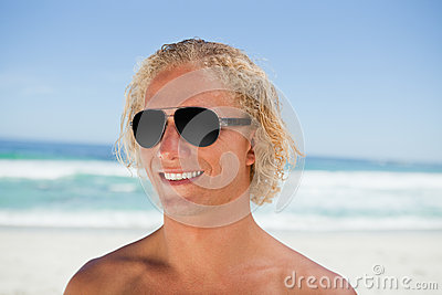Smiling man wearing sunglasses while standing on the beach