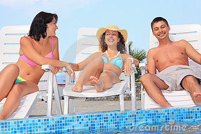 Smiling man and women reclining on chaise lounges
