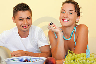 Smiling man and young woman eat fruit in cosy room