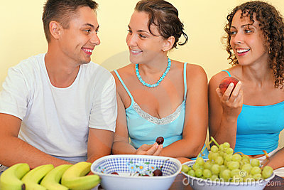 Smiling man and young women eat fruit in cosy room