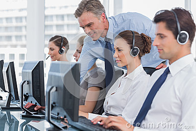 Smiling manager helping call centre agent