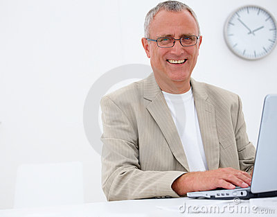 Smiling mature business man using a laptop