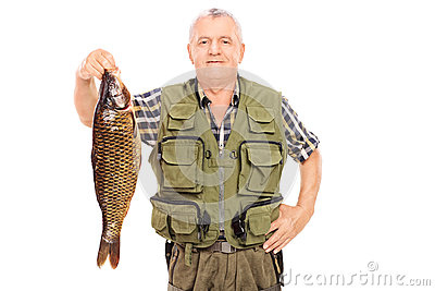 Smiling mature fisherman holding a big fish