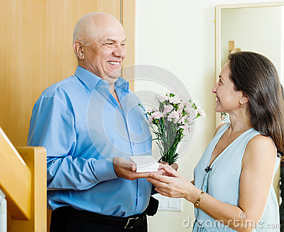 Smiling mature man giving jewel  to woman