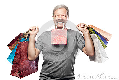 Smiling mature man holding shopping bags isolated on white