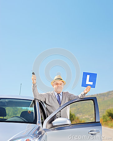 Smiling mature man posing next to his car holding a L sign and k