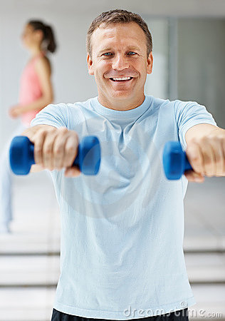 Smiling mature man using dumbbells at the gym