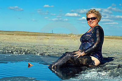 Smiling mature plump woman taking mud treatment
