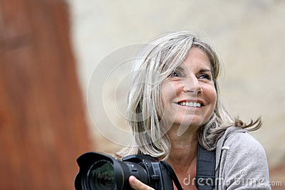 Smiling mature woman holding a camera
