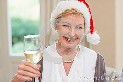 Smiling mature woman in santa hat toasting with white wine stock photo