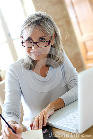 Smiling mature woman working from home royalty free stock for Household bargaining and the design of couples income taxation