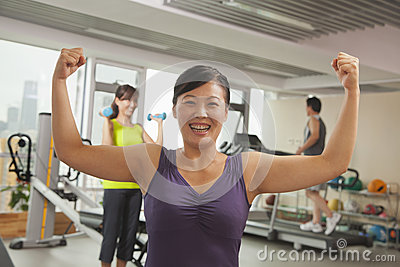 Smiling mature women showing her strength after workout in the gym, arms raised and flexing muscles