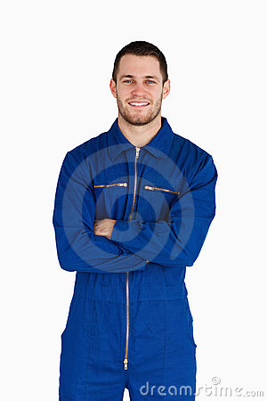 Smiling mechanic in boiler suit with folded arms