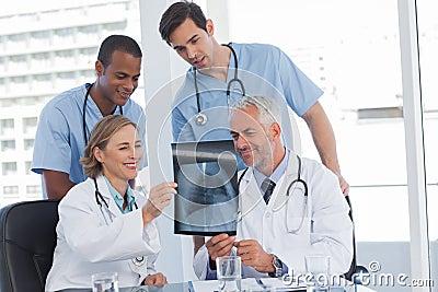 Smiling medical team examining radiography