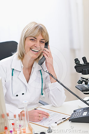 Smiling middle age doctor woman speaking phone