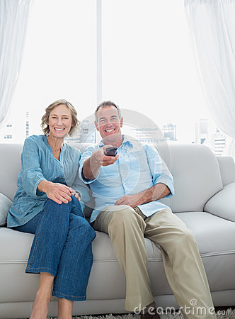 Smiling middle aged couple sitting on the couch watching tv