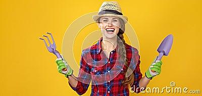 Smiling modern woman farmer showing gardening tools Stock Photo