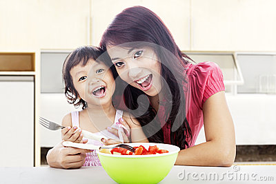 Smiling mom and daughter in kitchen