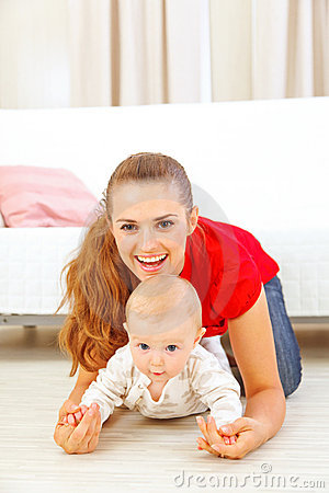 Smiling mommy and adorable baby playing on floor