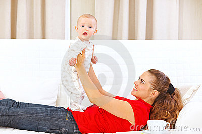 Smiling mother and adorable baby playing on divan