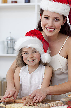 Smiling mother and daughter baking Christmas cakes