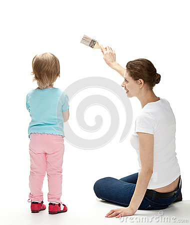 Smiling mother and  daughter painting the wall
