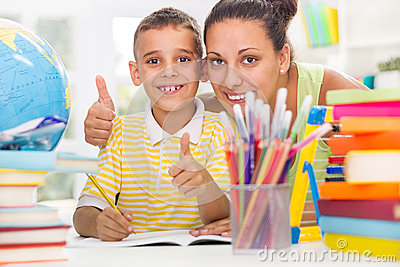 Smiling mother helping son to do his homework