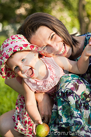 Smiling Mother and her daughter in summer park.