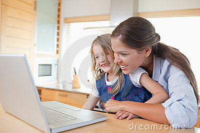 Smiling mother and her daughter using a laptop