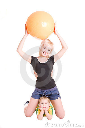 Smiling mother and her son with a fitness ball on
