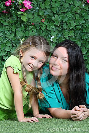 Smiling mother and little daughter lie on lawn in garden